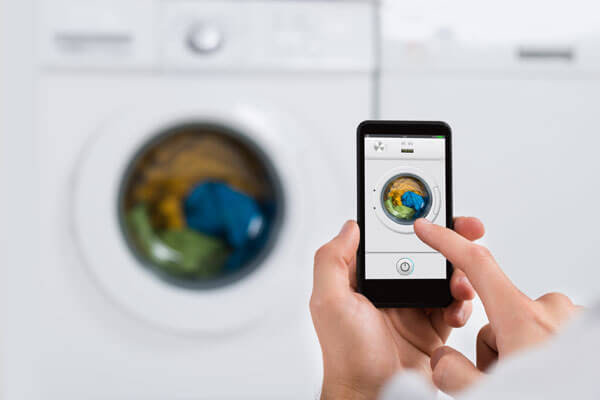 A person using a mobile app to control their washing machine