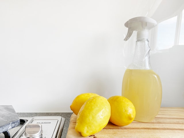 3 lemons by a stove top and a bottle of white vinegar and lemon solution