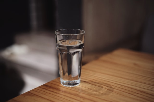 water filled glass on the edge of a wooden table
