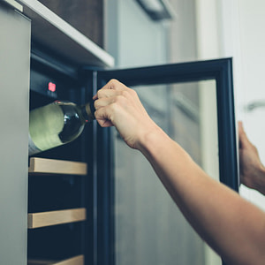 A person removing wine from a wine cooler
