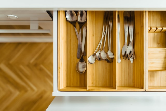 open drawer with pine cutlery organiser with spoons and forks