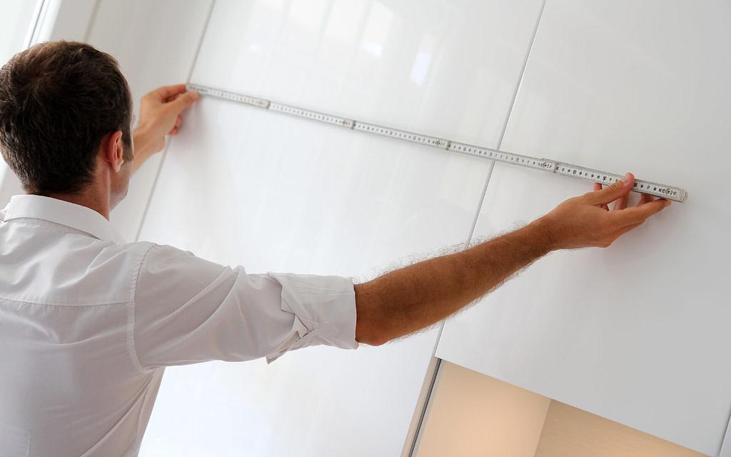 Man measuring a kitchen space