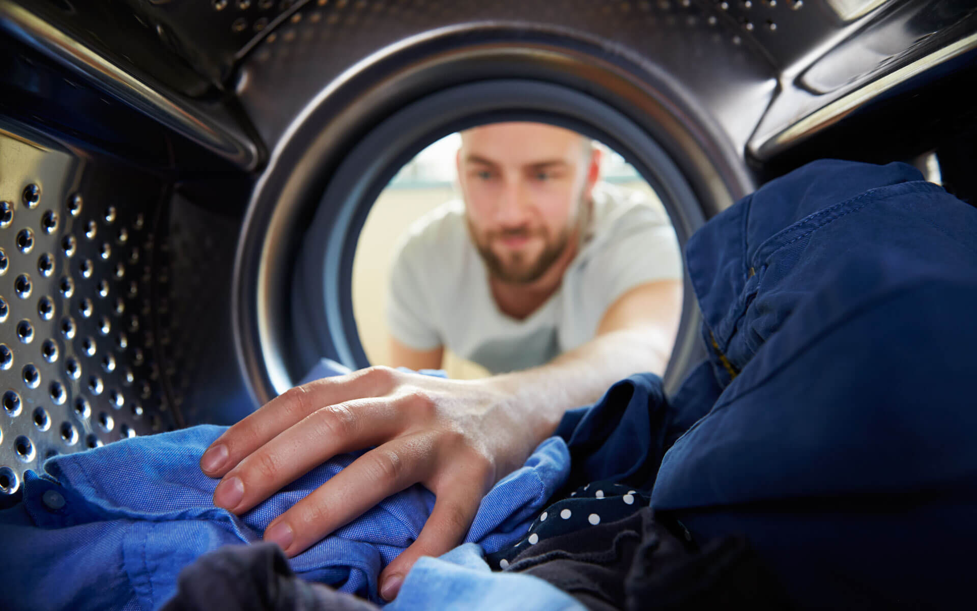 Man reaching into a tumble dryer