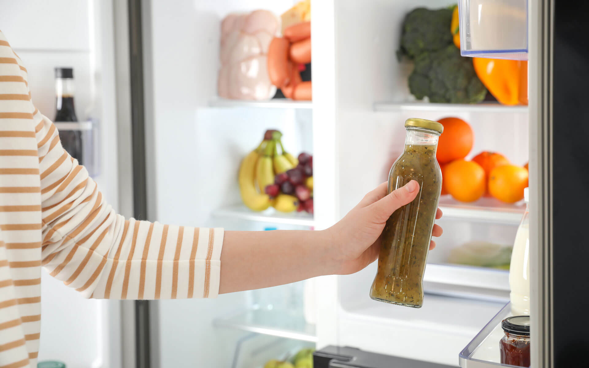 A person grabbing a bottle of sauce from a fridge