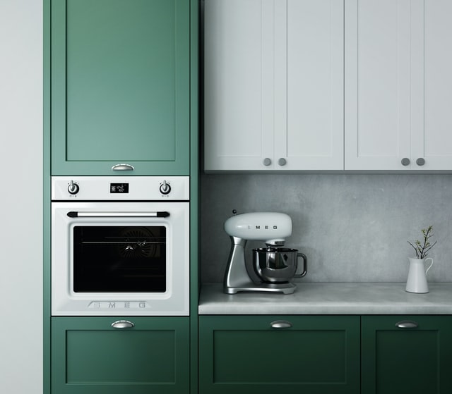 integrated smeg cooker in green cupboards with a smeg mixer on the countertop