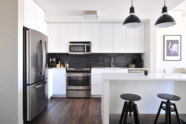white kitchen cupboards, with stainless steel appliances in an L shape with a counter on the right