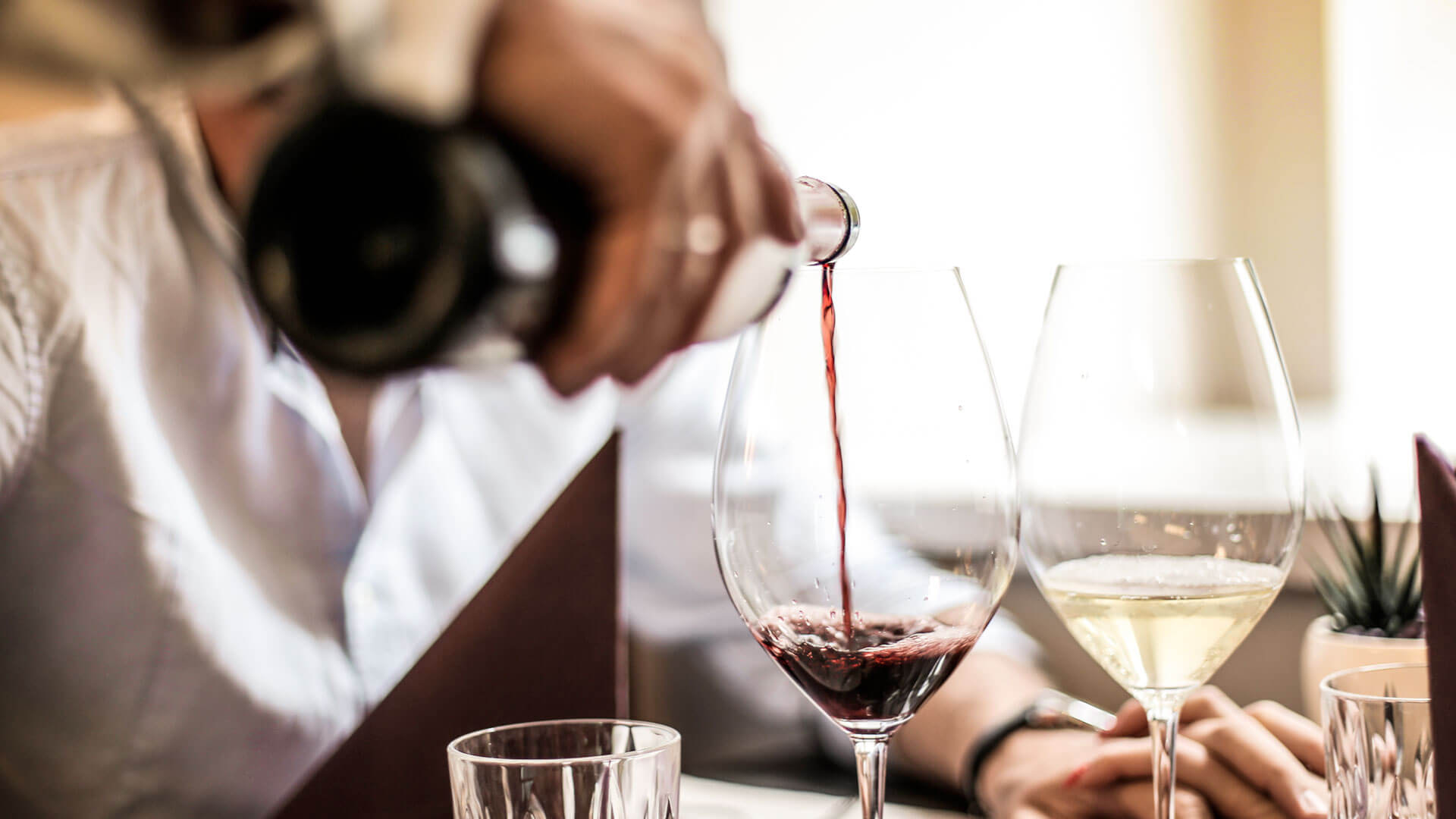 Red wine being poured into a glass at the table