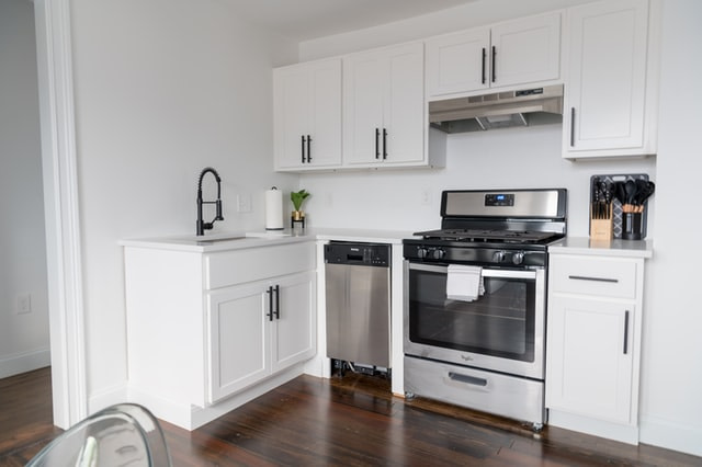 whit kitchen cupboards and white kitchen appliances in an L shape layout