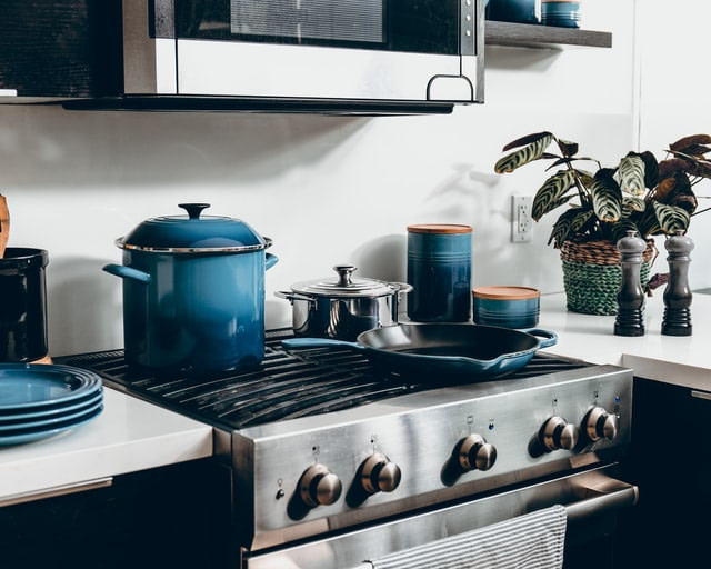 stainless steel cooker adorned with blue pans and crock pot