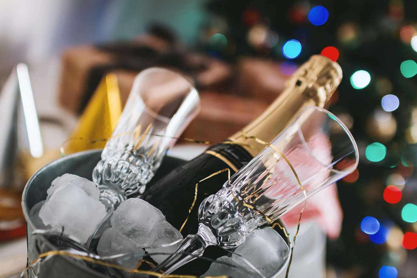 bottle of champagne in an ice bucket with two glasses and christmas tree in the background