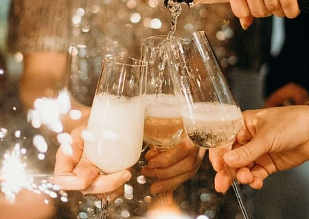 champagne pouring into several glasses people hold out