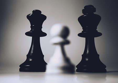 close up of chess game with small white pawn against black king and queen