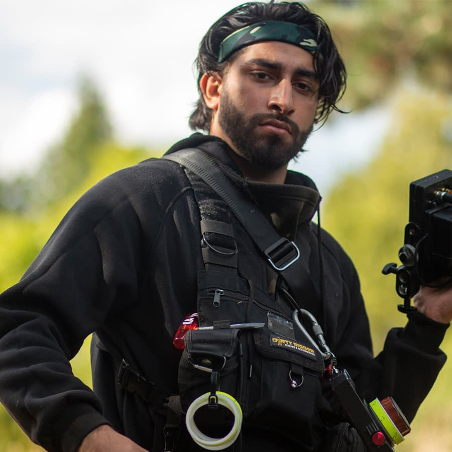 Riaz wearing our LED Chest Rig on a film set with gaffer tape attachments and holding a film camera