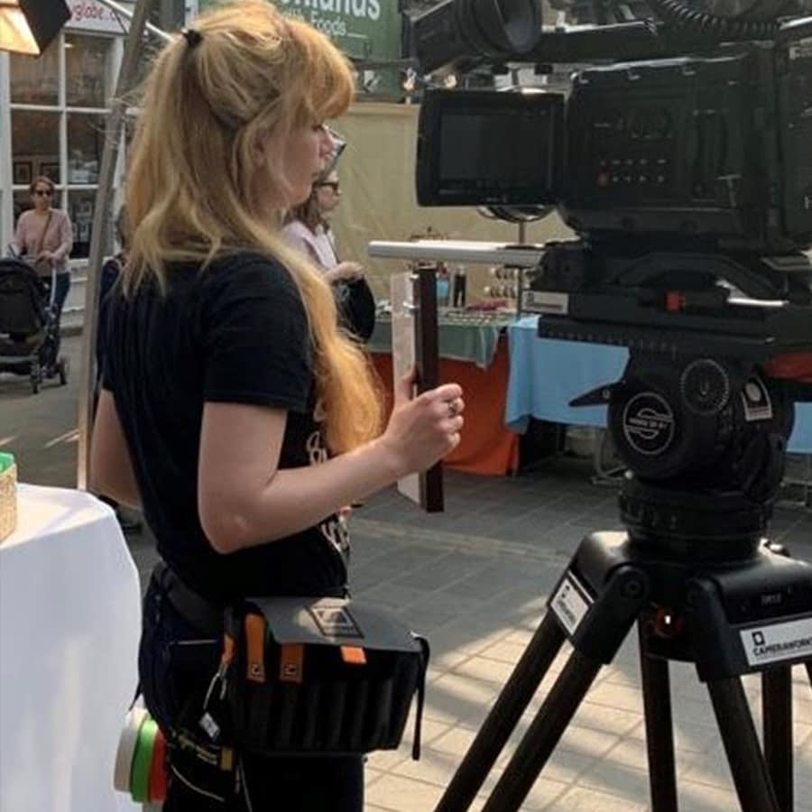 Camera assistant Bianka on set with a gaffer tape attachment and Dirty Rigger comfort fit gloves, gaffer tape and AC bag