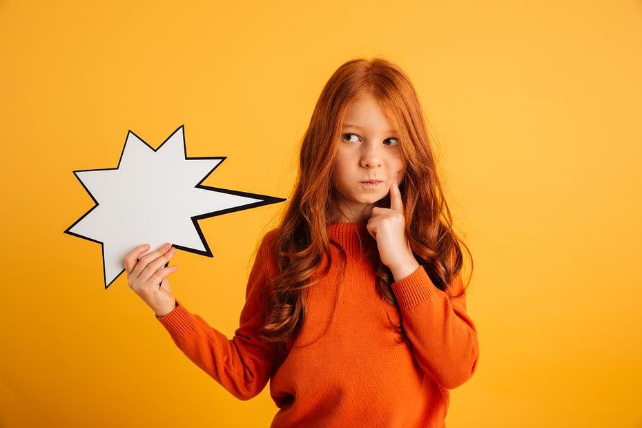 Thinking little redhead girl holding speech bubble.