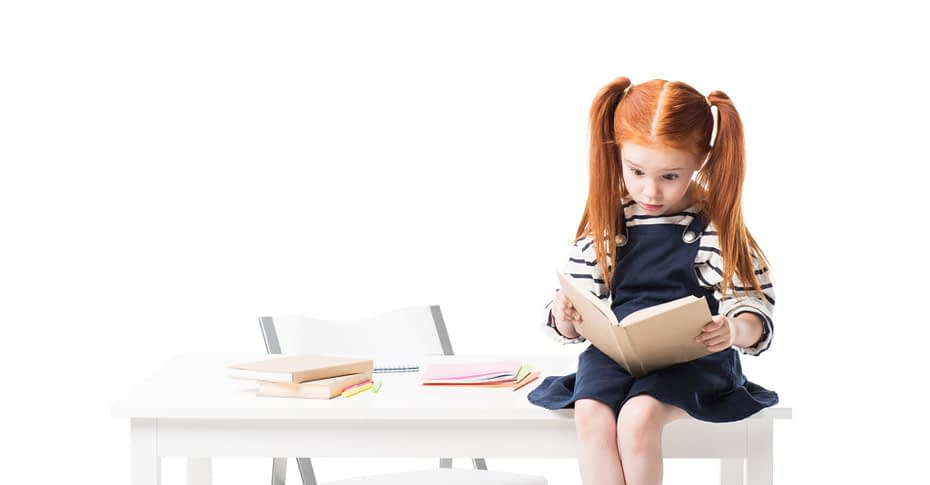 Little girl reading books on a table