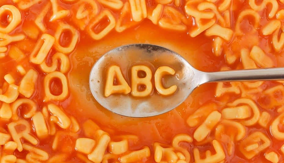 Pasta shaped ABC letters in tomato sauce on a spoon