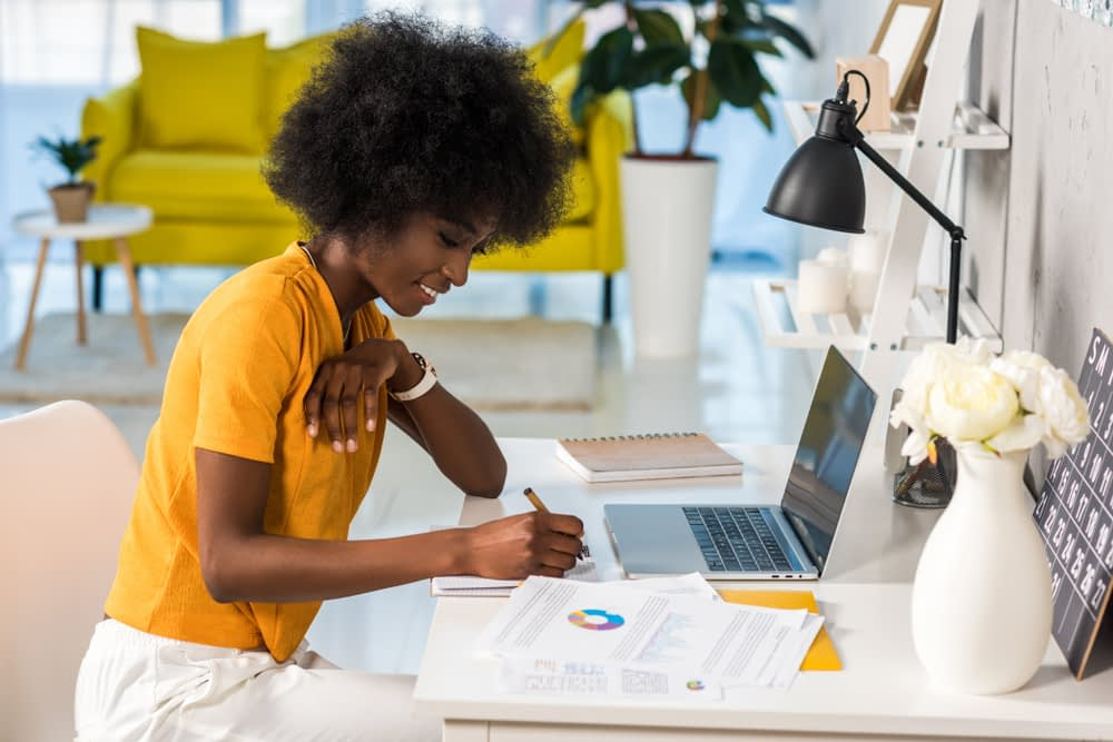 A woman sat at a desk making notes